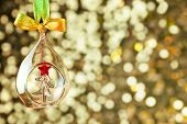 Christmas magic golden background with glass bauble and colorful ribbon - copy space for text