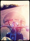 Riding on motorcycle with view of road - instagram effect