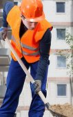 Construction Worker Digging Sand With Shovel