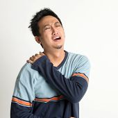 Asian man neck muscle sprain, or shoulder pain, on plain background