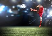 Young football player on stadium kicking ball in jump