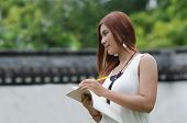 Beautiful Young Redhead Woman Writing In A Notebook