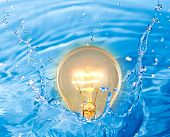 Glowing yellow light bulb of idea in water