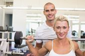 Personal male trainer helping young woman with lifting barbell in the gym