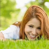 Portrait of a pretty redhead smiling and lying on grass in park