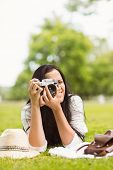 Smiling brunette lying on grass taking picture in the park