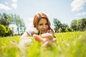 Pretty redhead happy and lying on grass in park