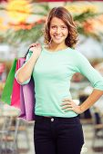 Pretty girl with shopping bags smiling at camera