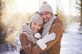 Amorous couple in winterwear embracing in snowfall