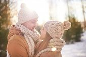 Young amorous couple in winterwear looking at one another outdoors