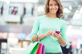 Cute female with shopping bags and cellphone