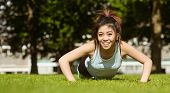 Portrait of happy healthy young woman doing push ups in park
