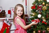 Little girl holding present box near fir tree on Christmas decoration background