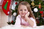 Little girl lying on fur carpet on Christmas tree background