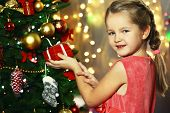Little girl decorating Christmas tree on bright background