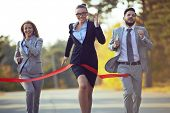 Competitive businesswoman coming to finish first with her colleagues behind