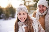 Cute girl in winterwear looking at camera on background of her boyfriend in winter park