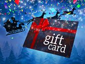 Santa flying his sleigh behind gift card against snowy landscape at night