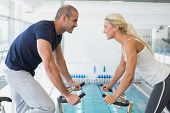 Side view of smiling fit couple working on exercise bikes at the gym
