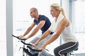 Determined fit young couple working on exercise bikes at the gym