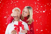 Loving couple with gift against red background