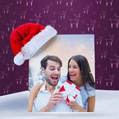 woman surprising boyfriend with gift against purple reindeer pattern