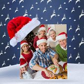 Father in santa hat carving chicken at christmas dinner against blue reindeer pattern
