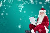 Santa sits and uses a laptop against green snowflake background