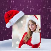 festive blonde smiling at camera against purple reindeer pattern