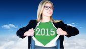 Businesswoman opening shirt in superhero style against bright blue sky over clouds