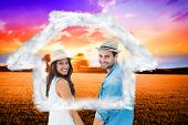 Happy hipster couple holding hands and smiling at camera against countryside scene
