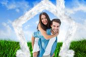 Happy hipster giving his girlfriend a piggy back against field of grass under blue sky