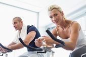 Portrait of a fit young couple working on exercise bikes at the gym