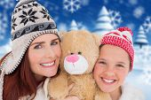 Mother and daughter with teddy against blurred winter scene