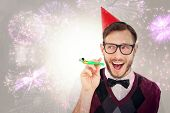 Geeky hipster in party hat with horn against colourful fireworks exploding on black background