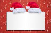 Santa hat on poster against red reindeer pattern