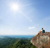 Hiker relaxing on top of the mountain at sunny day