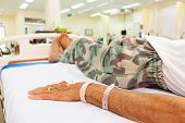 stock photo of emergency treatment  - elderly patient lie down on bed in emergency room in rural hospital  - JPG