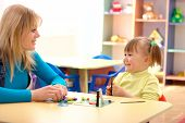 picture of nursery school child  - Teacher and cute little girl play with plasticine in preschool - JPG