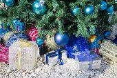 Colorful Christmas Gift Boxes Under The Christmas Tree Decorated With Baubles And Tinsel