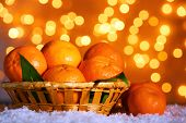 Fresh ripe mandarins on snow, on lights background