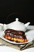 Tasty eclairs and pot of tea on wooden table, on black background