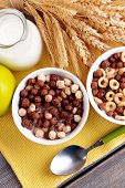 Various sweet cereals in ceramic bowl, fruits and jug with milk on napkin, on color wooden background