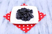 Squared white plate of prunes on polka-dot napkin on color wooden background