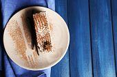 Tasty tiramisu cake on plate, on wooden table