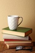 Pile of books with cup and glasses on wicker surface and light wall background
