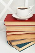 Pile of books with cup of hot drink on the chair on brick wall background