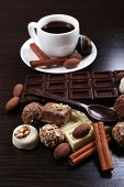 A Cup of coffee and a saucer with chocolate spoon, on the dark wooden smooth background