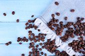Coffee beans on jeans material with fringe on blue wooden background