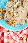 Sunflower halva with nuts on plate, on wooden background